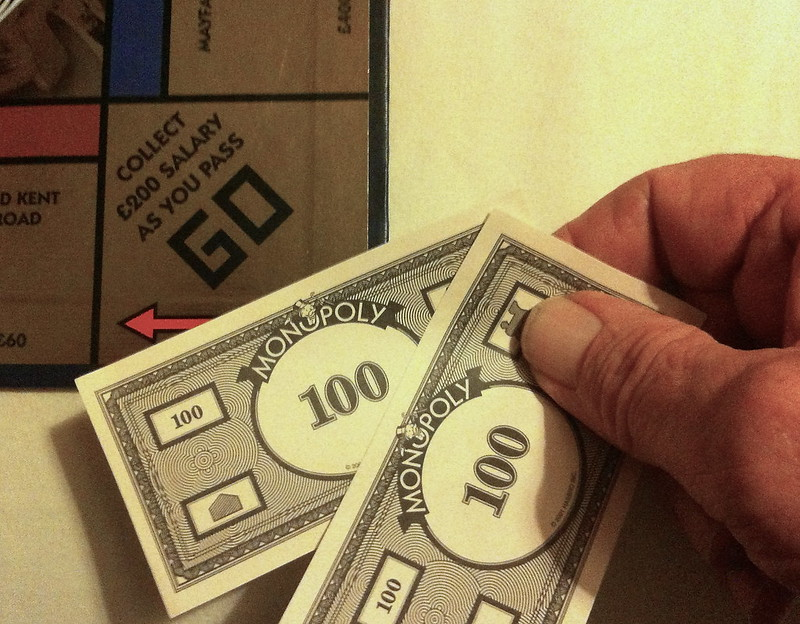 """Two one-hundred dollar Monopoly bills over the """"Collect $200 Salary as you pass Go"""""""