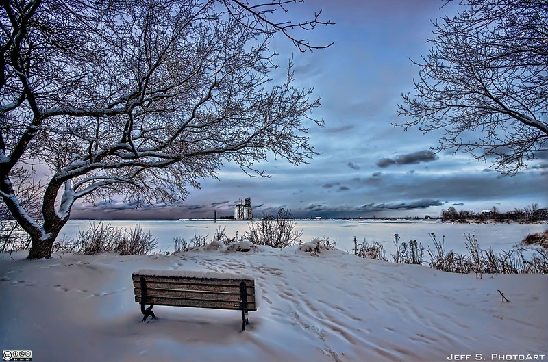 Winter view with a bench in the foreground in front of a lake with snow on the ground and in the trees.