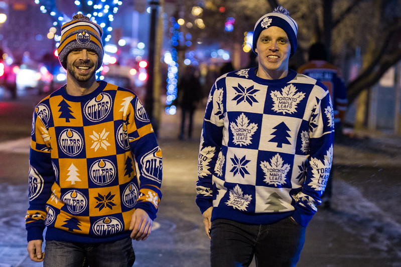 Two young men walking in Edmonton; one wearing #Oilers sweather and tuque, the other with #MapleLeafs sweater and tuque.