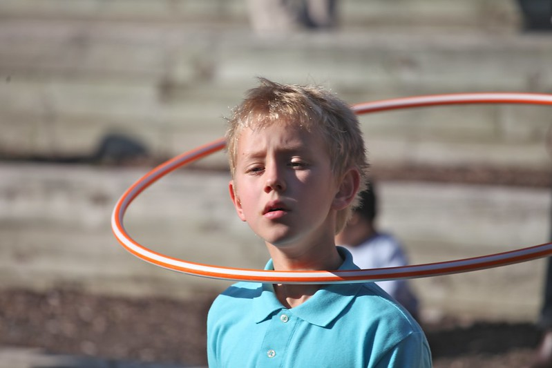 Young boy with a hula hoop suspended above his shoulders with a casual look.