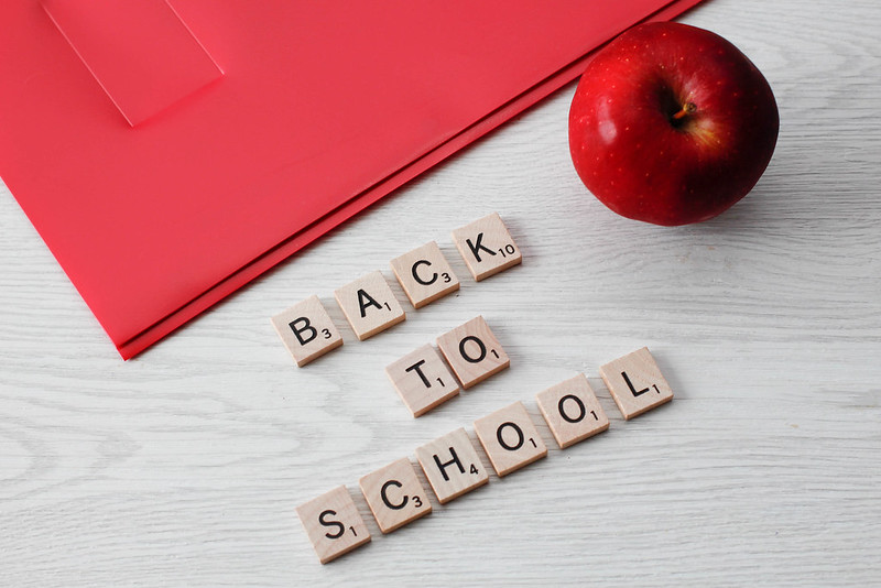 """Back to School"" spelled out with Scrabble letters by a red apple and a red binder."