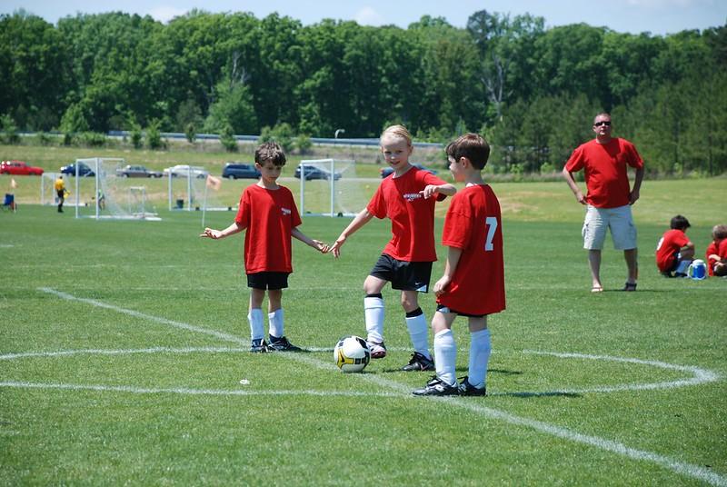 Three youth soccer (futbol) players at a kickoff.