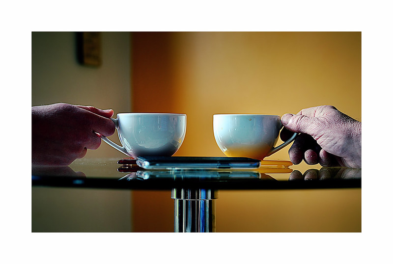 Closeup of two hands holding coffee cups on a small class table top.