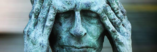 Closeup of a bronze statue which appears to be holding its head with both hands as if with a headache.