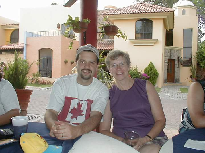 Sitting with my mom at a dinner party back in 2001, outside with houses in the background.