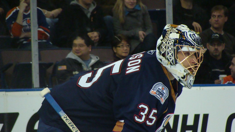 Close up photo of Edmonton Oilers goalie Dwayne Roloson with crowd visible in the background.