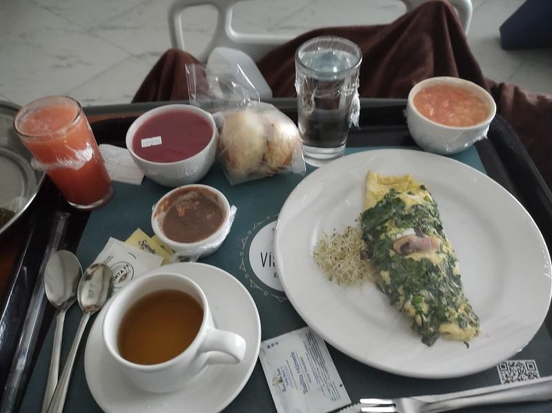 Tray of breakfast in the hospital: omelette, tea, juice, fruit, jello, break, glass of water.