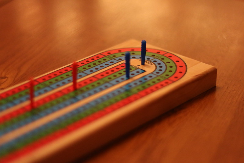 Closeup of cribbage board showing blue winning by 9 points against the red pegs.