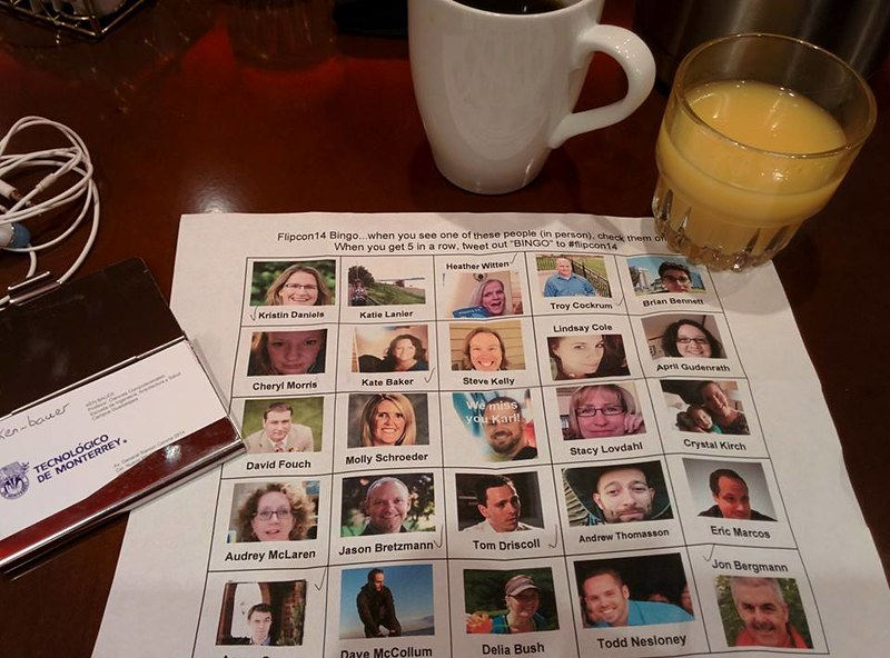 My business cards, coffee, orange juice surrounding the FlipCon14 bingo card which has images of 25 speakers at that event.
