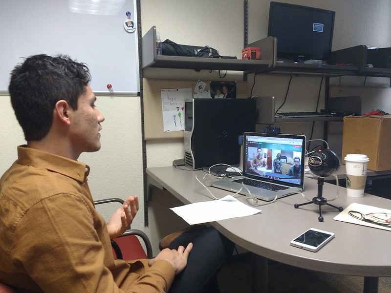 Student in an office in a Google Hangout using a laptop.