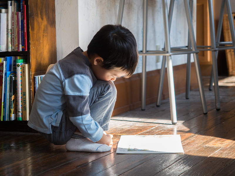 A young child crouched in a full squat on a hardwood floor reading what appears to be a newspaper in laying  in a beam of sunlight on the floor.