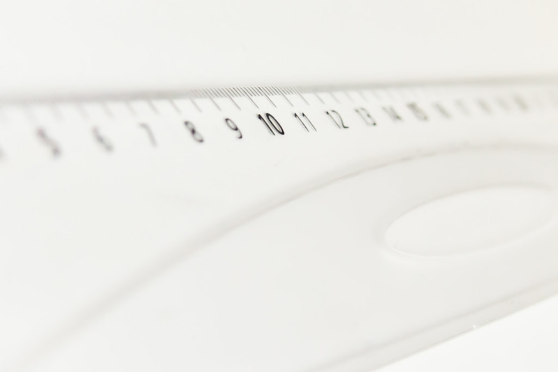 Close up of a clear ruler showing the numbers 6 through 20. Very shallow depth of field focused on the number 10.