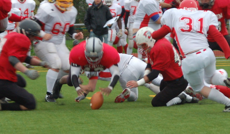 Various football players from both teams reaching out for a fumbled ball.