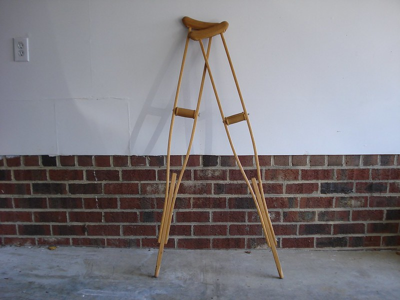 A pair of wooden crutches leaning against a white wall with brick base, resting on a concrete floor.