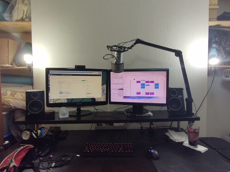 Desk with computer setup of two monitors on elevated shelf, mouse and keyboard and other random stuff on the desk. Microphone mounted to overhead stand in place. Two spot lights for webcam lighting on each side of the monitors.