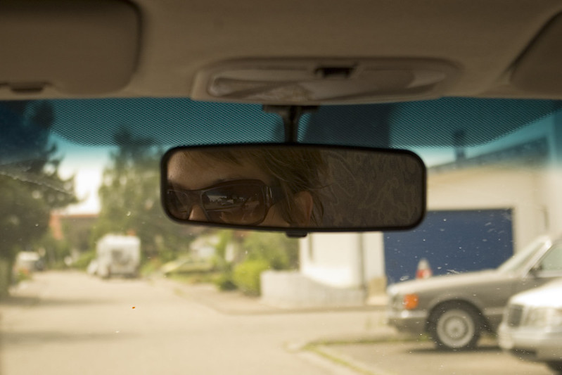 Close shot from back seat of a car with a view of the drivers glasses via the rear-view mirror of the vehicle. Residencial street (out of focus from shallow depth of field) visible through the windshield.