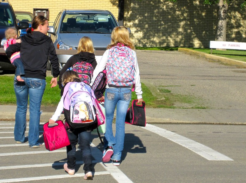 Parents with three children crossing the street in a crosswalk to enter a school.