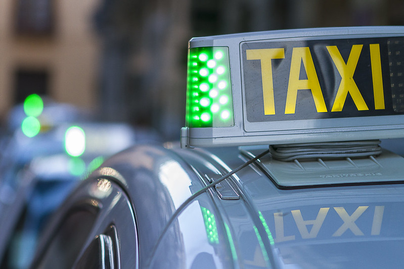 """Close-up of at """"TAXI"""" sign on top of a taxi cab."""