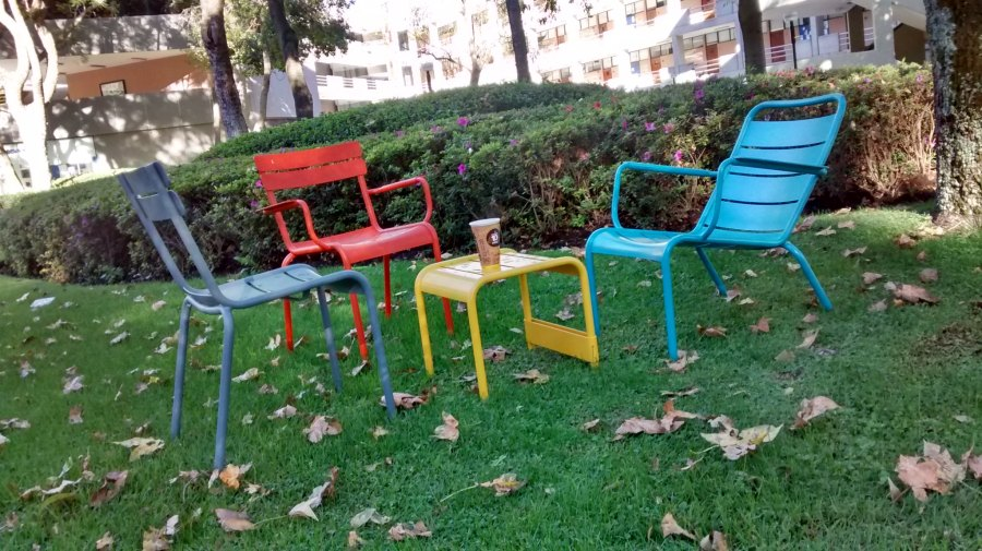 Three coloured (grey, orange, blue) metal lawn chairs arranged around a similar style yellow small table with a coffee on it. This on the grass in the gardens of the Tecnológico de Monterrey in Guadalajara.