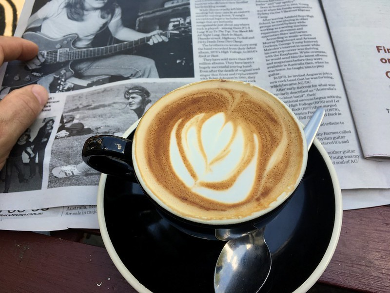 A flat white coffee in a black mug in front of a newspaper article about Malcolm Young of AC/DC.