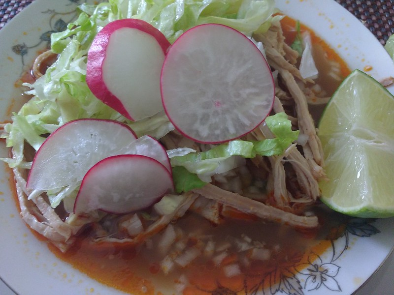 Close-up of a bowl of traditional Jalisco pozole garnished with lettuce, lime, and radishes.