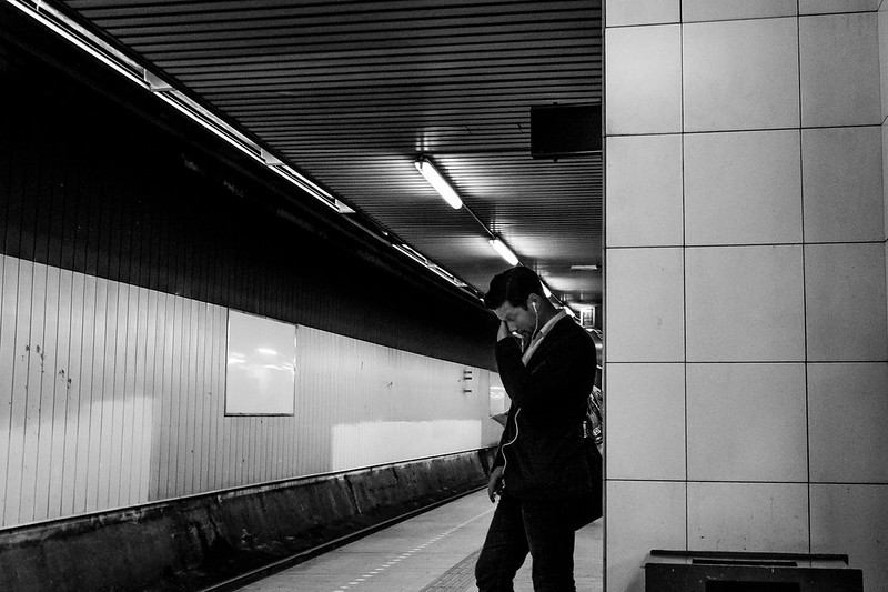 A black and white image of a man stading in a subway station while hold his head and appearing tired.