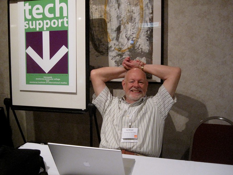 """Carl Berger sitting behind a conference event table in front of an Apple laptop with a """"Tech Support"""" sign behind and to his right."""