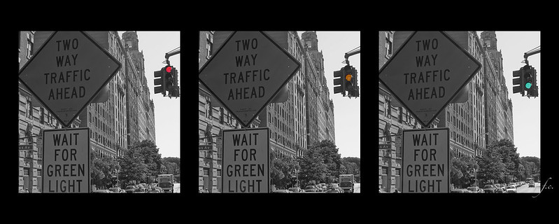 """Series of three shots, identical black and white steet scene focused on a pair of street signs """"Two Way Traffic Ahead"""" and """"Wait for Green Light"""". The first image has a colorized red of the traffic light, the second image with colorized yellow signal, and the third image with colorized green signal."""
