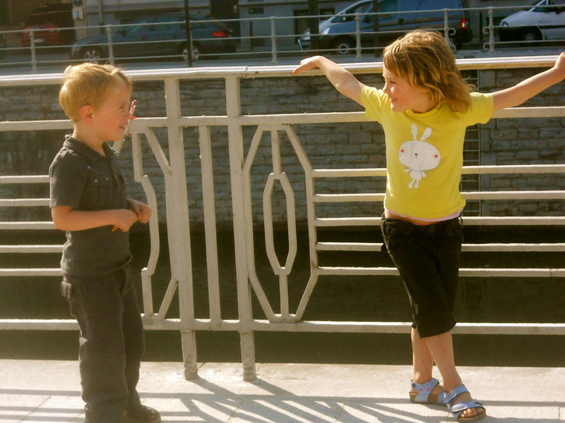 Two young children speaking to each other about 1 meter apart near a fence, one is leaning back against the fence with her arms up and out.