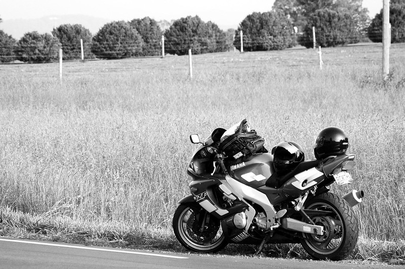 Black and white picture of a Yamaha sport motorcyle on the side of the road with long grass, fence and trees in the background.
