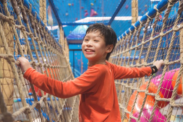 Young asian boy climbing the net at indoor playround and smiles