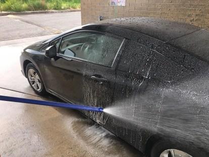 Applying ceramic sealant to a car.