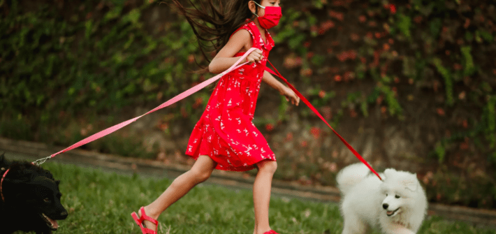 girl with mask running with dogs