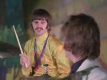 0:13. Para mí, la secuencia más importante de este promo. Conviene verla entera, la mirada sarcástica entre Ringo y John. Es de lo poco auténtico que se puede encontrar en el vídeo, junto con la expresión de George.