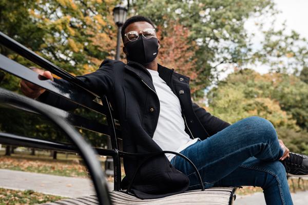 Homme assis sur un banc dans un parc durant l'automne