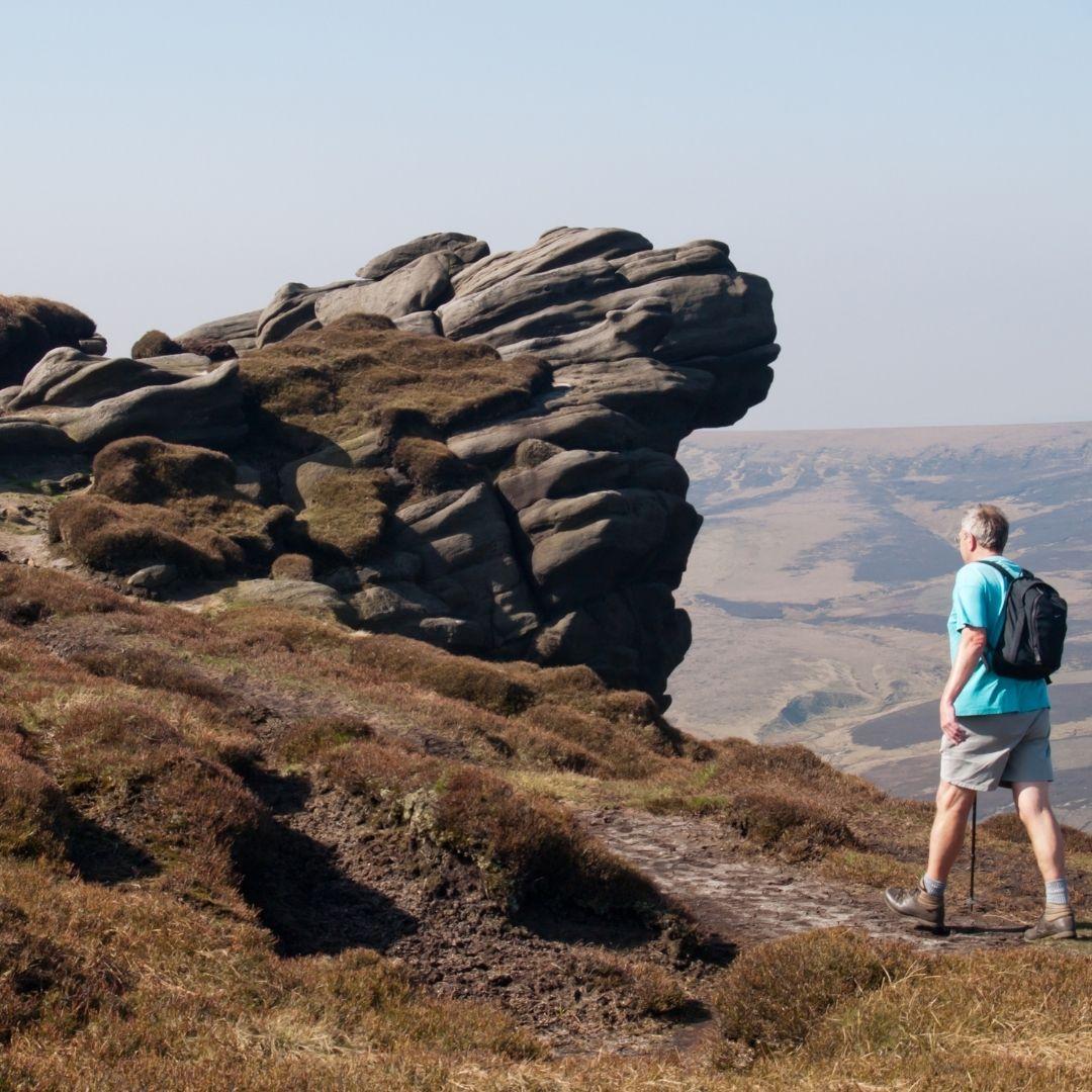 rambler walking near rock formation on kinder scout