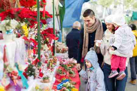 Smiling parents and little children buying red Euphorbia at Christmas fair. Focus on woman
