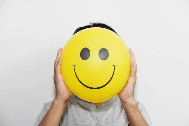 image montrant un homme tenant un ballon jaune au visage souriant devant lui sa tête, montrant ce qu'une personne ressentira une fois la réponse donnée à la question du temps nécessaire au fonctionnement de l'huile de CBD