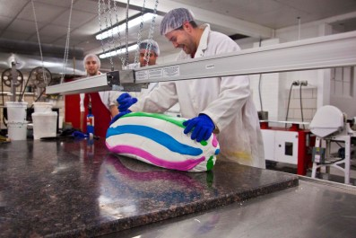Dauphin and Shawn Freeder supervise Paul Freeder adding stripes to a custom mint batch. At size, the stripes will appear evenly on the top and bottom of the candies.