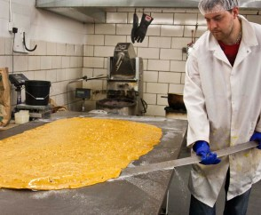 Wielding a large, flat stainless steel bar, Paul stretches each batch of brittle by hand.