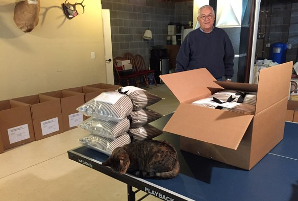 """The couple's cat gets in on the """"quality control,"""" as Allan looks on."""