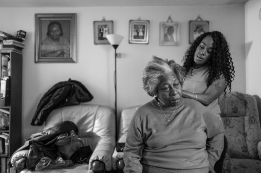 Hermine Grocia has her hair plaited at home in Brixton, April, 2018 by Krystyna, one of her 11 granddaughters. Every Friday evening is open house; the family, often four generations, catch up and share food. 'It sometimes finishes as late as 2am,' Hermine says. 'Sometimes they'll dance. They'll roll up the carpet and put it behind the settee'