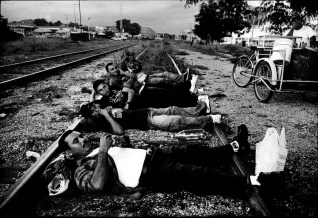 A group of Illegal migrants from El Salvador lie on the railway track while waiting for a cargo train which carries illegal migrants to the U.S. - Mexico border. This group was robbed of most of their money by Mexican police while crossing the border from Guatemala.