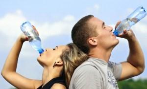 Un hombre y una mujer beben agua directamente de la botella