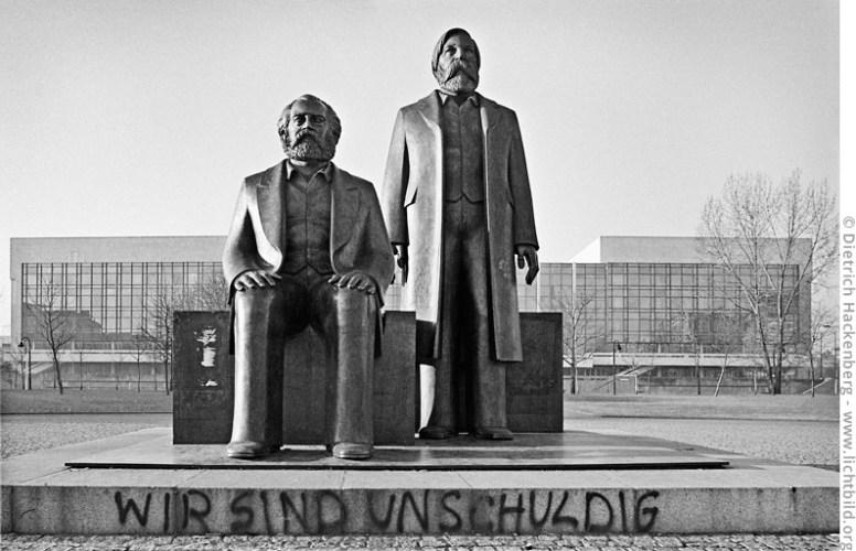 """Wir sind unschuldig — Graffiti auf der Marx und Engels Skulptur vor dem """"Palast der Republik"""" kurz nach der Wiedervereinigung. Foto © Dietrich Hackenberg"""