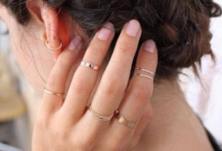 Gold stacking rings on a woman's hand.