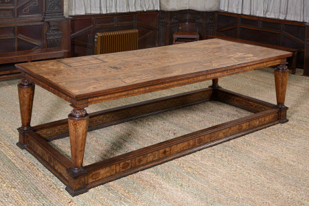 Eglantine table. Oak table with inlaid walnut rectangular top. four conical legs, tapered from top, also inlaid, as is frieze and stretchers with moulded edges. Legs have carved capitals with egg and dart moulding above a gadrooned ring. Plinth foot is squared. Inside of stretchers painted strapwork pattern. Outside diamond and oval pattern. Frieze inlay has metopes and drops with roundels between. Top inlaid with musical instruments, etc.