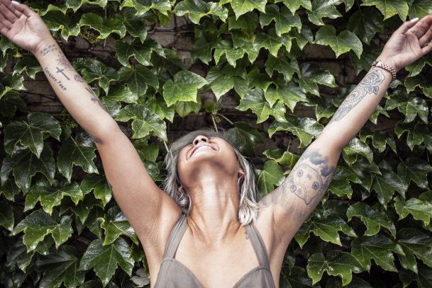 Happy woman with tattoos smiles and stretches arms upward.