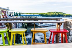 Colorful Vivid Chairs Painted Green, Yellow And Orange On Waterf