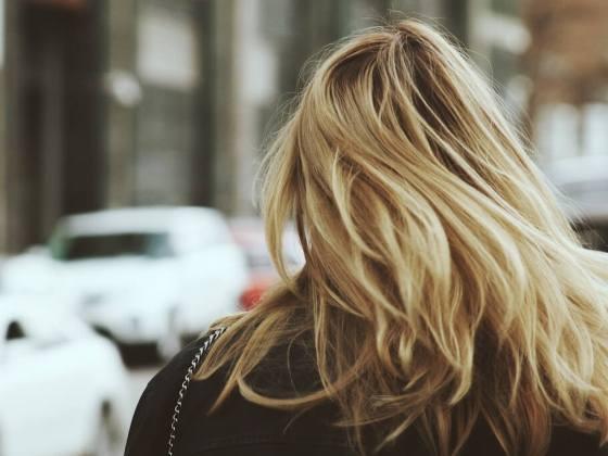 eine Frau mit blonden Haaren von hinten